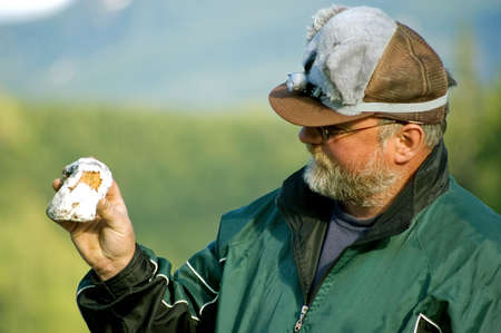 This middle aged man is wearing a goofy koala bear hat while showing off a unique rock he found in the mountains. Stock Photo - 4847824
