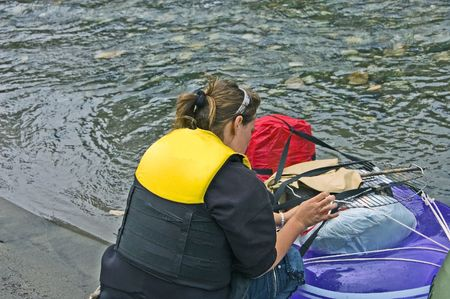 This young woman is making preparations for camping using a small boat upon the shore. photo
