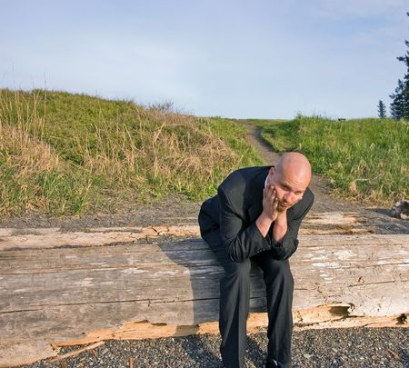 This young groom is nervous and stressed about pre wedding jitters.  Shown here sitting on driftwood at a beach. Stock Photo - 4871754