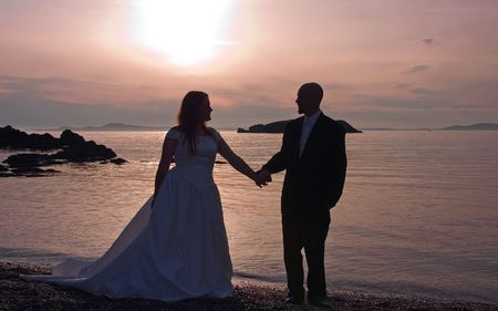 This lovely photo is a silhouette of a bride and groom holding hands at sunset on a beach overlooking the ocean. photo