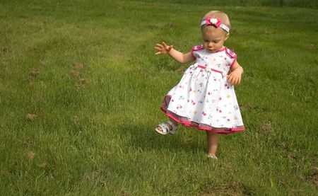 liking: This cute toddler girl is stepping high in the long grass, not liking it touching her legs. Stock Photo