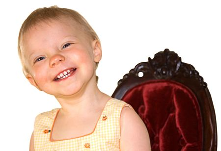 This one year old toddler girl is smiling in a burgundy colored princess type chair on a white background. photo