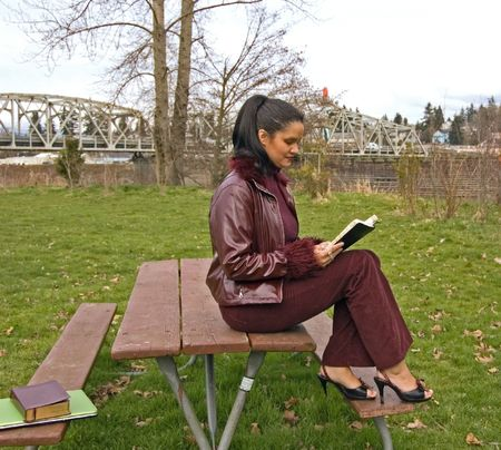 This attractive multi ethnic woman is sitting on a picnic table in a park reading wearing high heels and a burgundy colored leather coat. photo