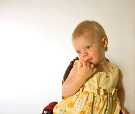 coy: Photo of a sweet little 1 year old Caucasian girl with blond hair sitting on a chair with a shy, coy facial expression. Stock Photo