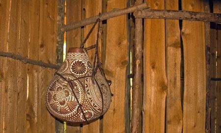 This African styled pottery is hanging with its intricate designs in a wooden room. Imagens