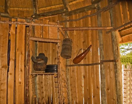 This old African styled tools and equipment are hanging inside a wooden hut. Imagens