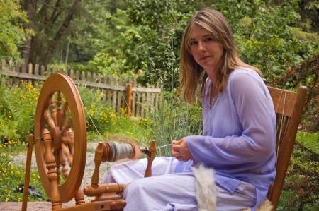 Esta mujer de raza cauc�sica est� hilando lana en una rueca en hilado artesanal casera como artesano en la acci�n.