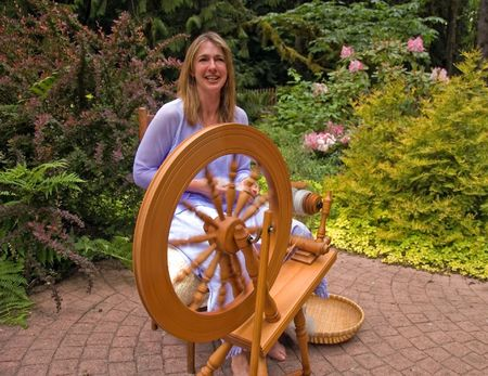 homespun: This artisan woman is hand crafting wool into homespun yard using a spinning wheel in a beautiful garden setting.