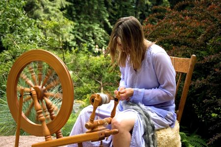 skilled: This woman in action is making homemade yarn with a spinning wheel from raw wool for a unique hand crafted work.  Shot in a beautiful garden setting.