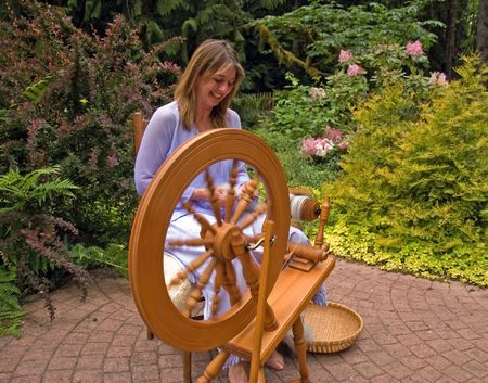 wheel spin: This woman is enjoying creating her craft of spinning raw wool into yarn with a spinning wheel in a peaceful garden.