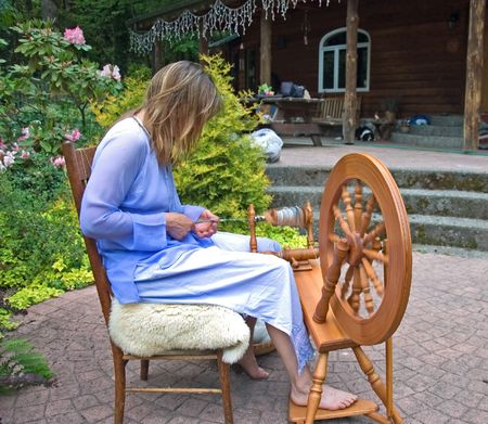 homespun: This artisan woman is hand crafting wool into homespun yard using a spinning wheel at her home in which she is self employed in this as a business.