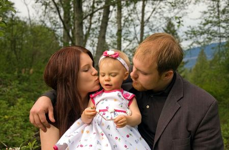 This cute young Caucasian family is outdoors together and mom is kissing baby girl while dad embraces both. photo