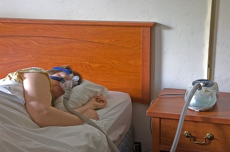 This middle aged Caucasian woman is sleeping with a CPAP machine on the bedside table while the mask is on her face, treating sleep apnea. photo