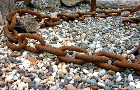 sized: This is a very large link rusty chain with rocks and pebbles in the background and foreground.