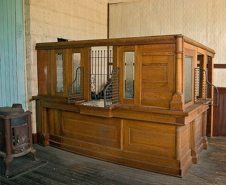 This antique bank teller station is an authentic replication with old wooden floors and wood stove to the old black typewriter in the background.