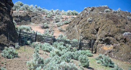 split rail: This landscape is an old wooden split rail fence between two large rock formations with a mountainous sagebrush area with bright blue sky. Stock Photo