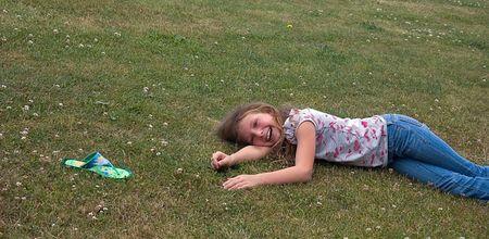 この 8 歳の少女は、草の中に敷設と遊んでいる間彼女のサンダルを失う後笑っています。 写真素材