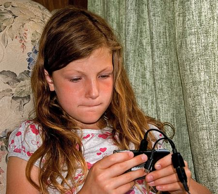 This 8 year old girl is playing an electronic game and has a candid facial expression of concentrating.