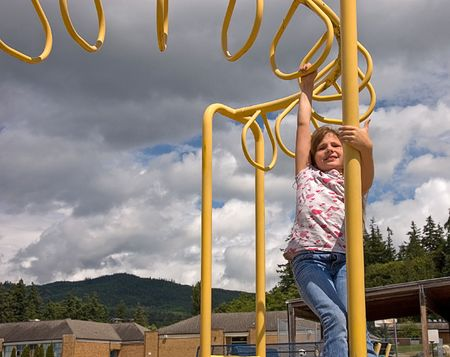 This 8 year old brunette girl is playing on the playground by swinging on overhead yellow ring structure. photo