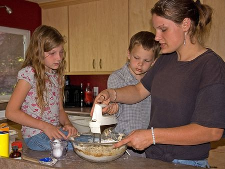This young mom is baking cookies with her son and daughter and having quality time together. photo
