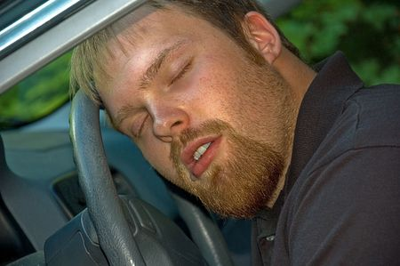 This young Caucasian man is asleep at the wheel of a car, with some drool beginning to run out of his mouth.