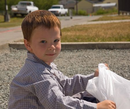 This 5 year old Caucasian boy is sitting outside with a white garbage bag. photo
