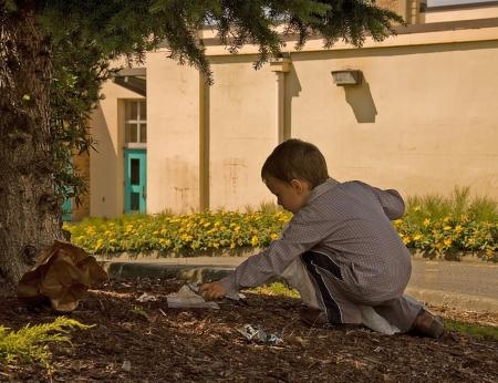 Este joven est� ayudando al medio ambiente, recoger la basura y ponerla en su bolsa de basura.