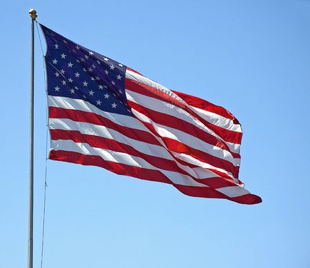 This American flag is flying its red, white and blue symbol against a bright blue sky. photo