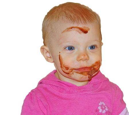 Cute little Caucasian with big blue eyes has chocolate pudding all over her face as shes learning to eat, isolated on a white background. photo