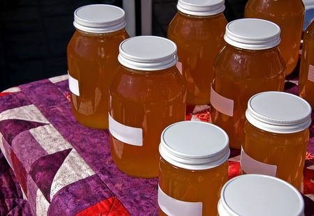 Table of many jars of fresh honey displayed on a homemade quilt. Stock Photo
