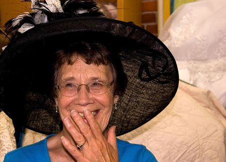 This elderly woman is laughing with joy while shopping and trying on this stunning vintage hat. photo