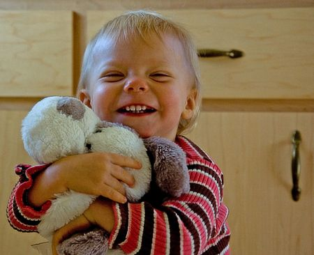 tightly: This toddler is very cute and hugging tightly her stuffed animal dog which she loves very much.