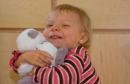 This cute toddler is hugging tightly her beloved stuffed animal dog with her facial expression showing happiness. Banco de Imagens
