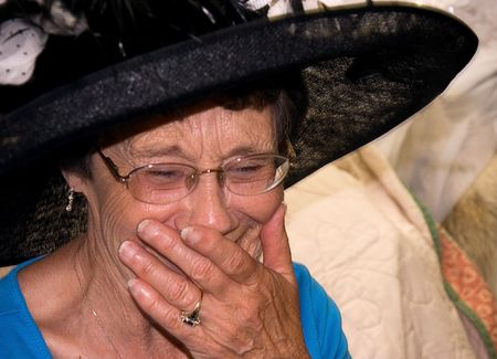 This elderly woman is laughing while wearing a black vintage hat and has her mouth covered with her hand.