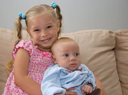 bi racial: These siblings are sitting together with baby brother being 2 months of age, and sister is 4 years old. Stock Photo