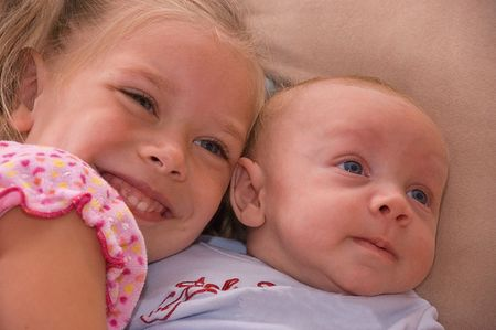 bi racial: This baby brother and 4 year old sister are sharing a moment together cuddling with affection and love.