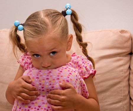 bi racial: This little 4 year old girl has part of her head buried on her knees with her big beautiful eyes looking up.