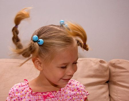bi racial: This little 4 year old girl is swinging her head to make her braided pigtails fly about.