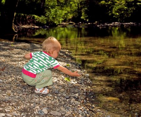 This young toddler girl is putting a rock into a beautiful wooded stream as shes discovering nature.