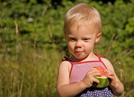This cute Caucasian toddler girl is eating a watermelon wearing a 4th of July themed dress. photo