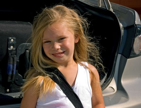 bi racial: This cute little 4 year old girl is getting ready for a trip standing behind a car packed with luggage. Stock Photo