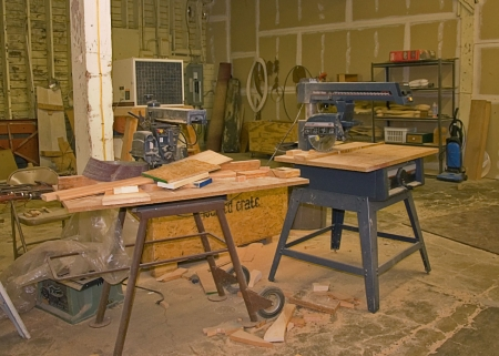 This room is a fully operational wood working shop complete with wood, tools, and other equipment.