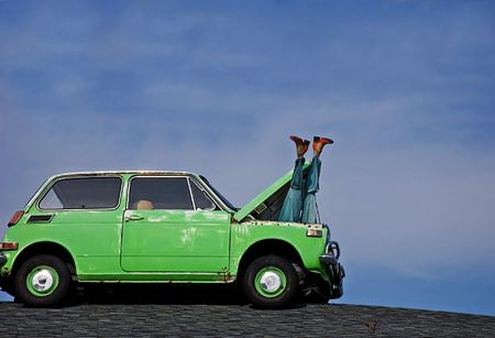 This humorous photo depicts a womans mannequin legs sticking out of the hood of a small green cars hood against bright blue sky.