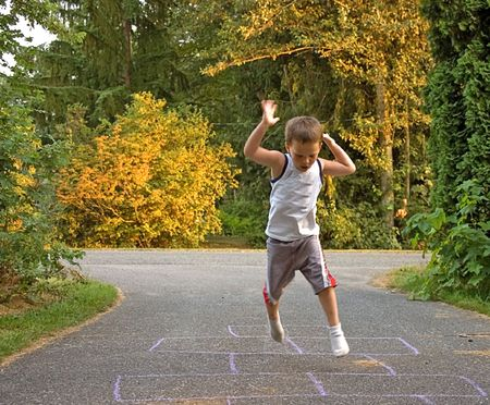 This little boy is caught in a jump mid air as he's playing hopscotch outdoors. Standard-Bild