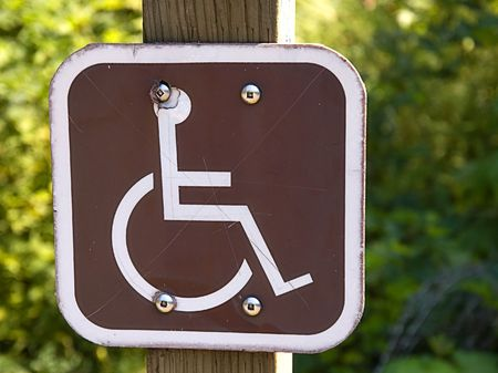 signalling: This sign with a wheelchair is brown and white signalling a symbol for the handicapped. Stock Photo