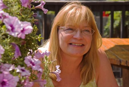 This middle aged blond woman is smiling and content sitting outdoors near basket of flowers and is happy.