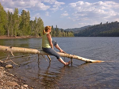 This woman is sitting on a tree log while enjoying a leisurely moment at a beautiful mountain lake. photo