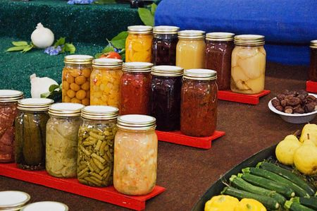This still life has rows of various home canned foods, pickles, vegetables, fruits and more.