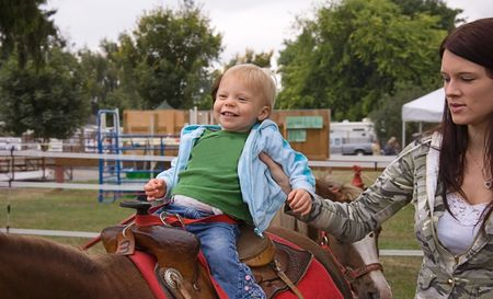 This happy toddler is on her first ever pony ride with young mom carefully guiding and holding her on. Stock Photo