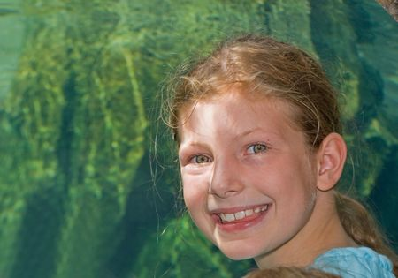 This pretty 9 year old Caucasian girl is smiling near a tropical aquarium, which really shows off her beautiful green eyes. Stock Photo - 5440139